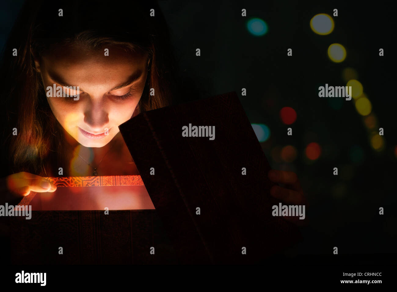 Young woman illuminated by light from within gift box - Stock Image