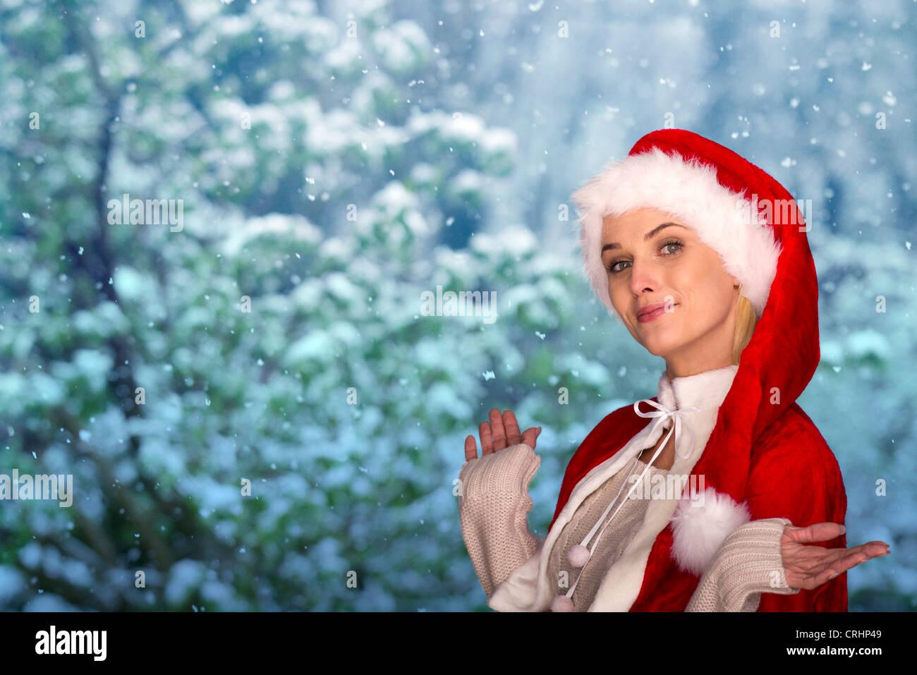 Woman wearing Santa hat, wintery scene in background, portrait - Stock Image