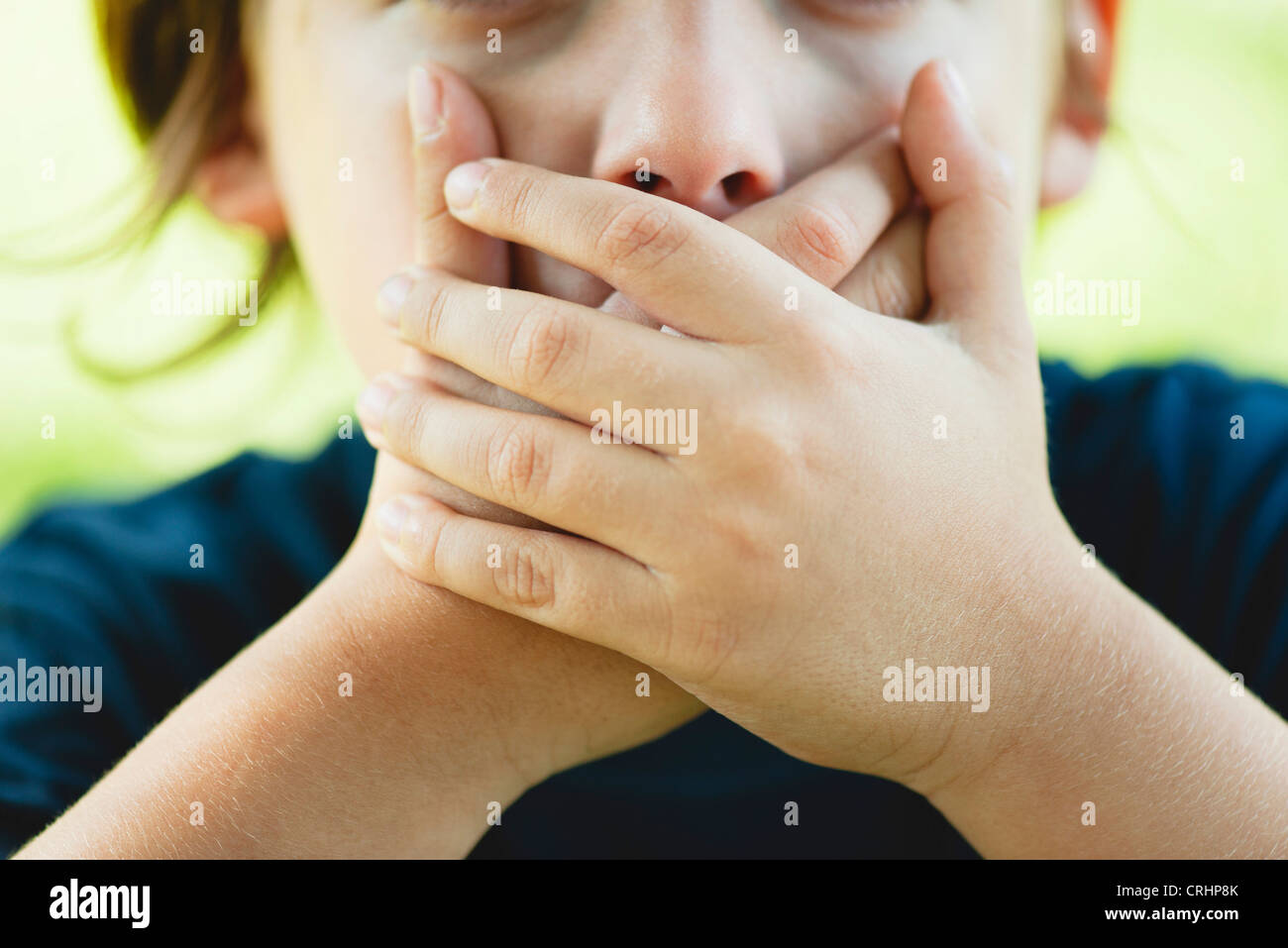 Boy covering mouth with hands, cropped Stock Photo