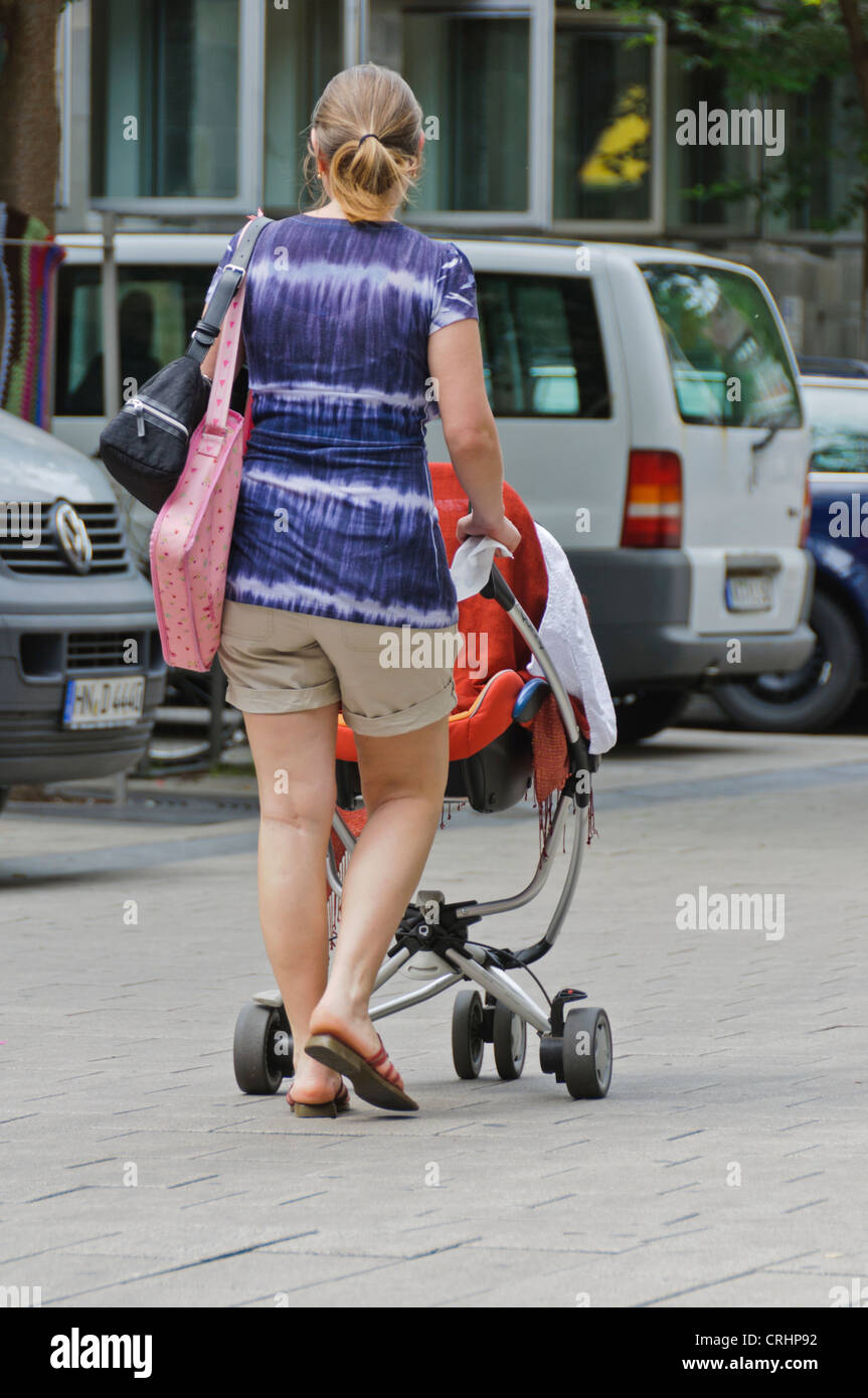 Woman with pony tail in shorts and batik T-shirt pushing baby carriage walking on street - Heilbronn, Germany - Stock Image