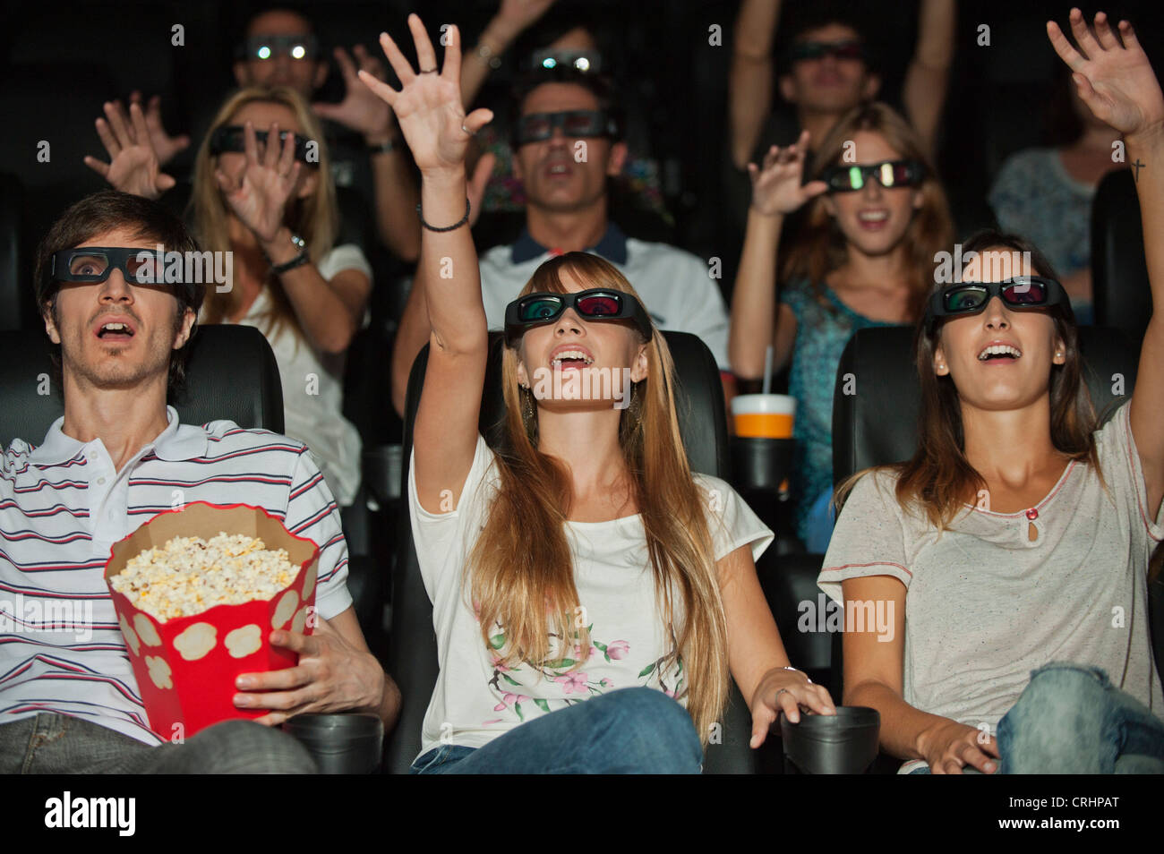 Audience wearing 3-D glasses in movie theater, arms reaching out - Stock Image