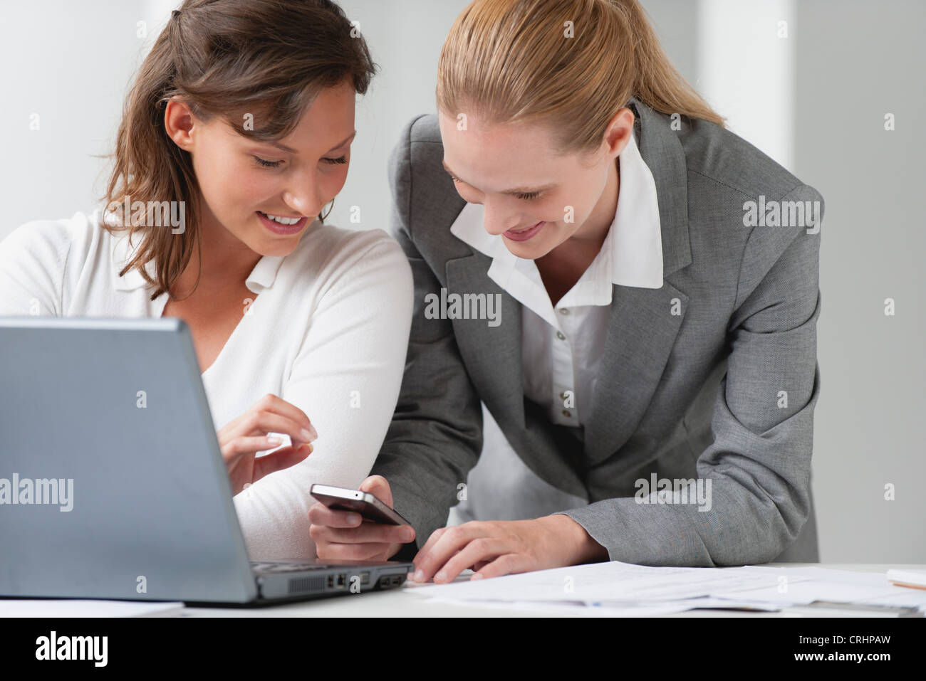 Business associates looking at cell phone Stock Photo
