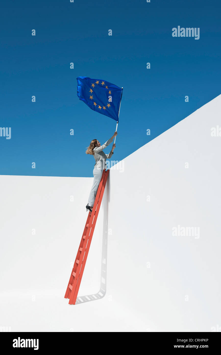 Businesswoman standing at top of ladder, holding European Union flag - Stock Image