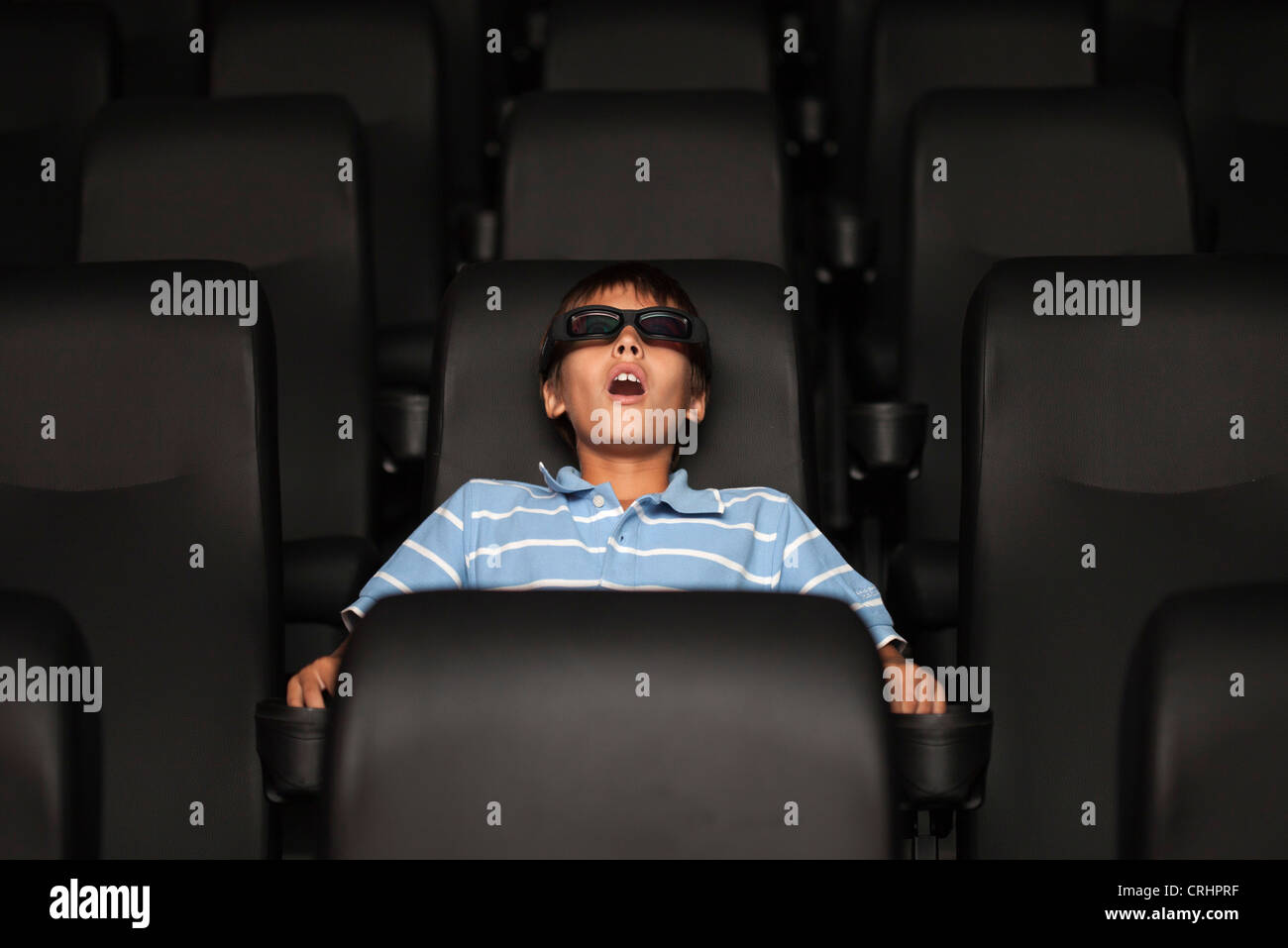 Preteen boy watching 3-D movie in theater - Stock Image