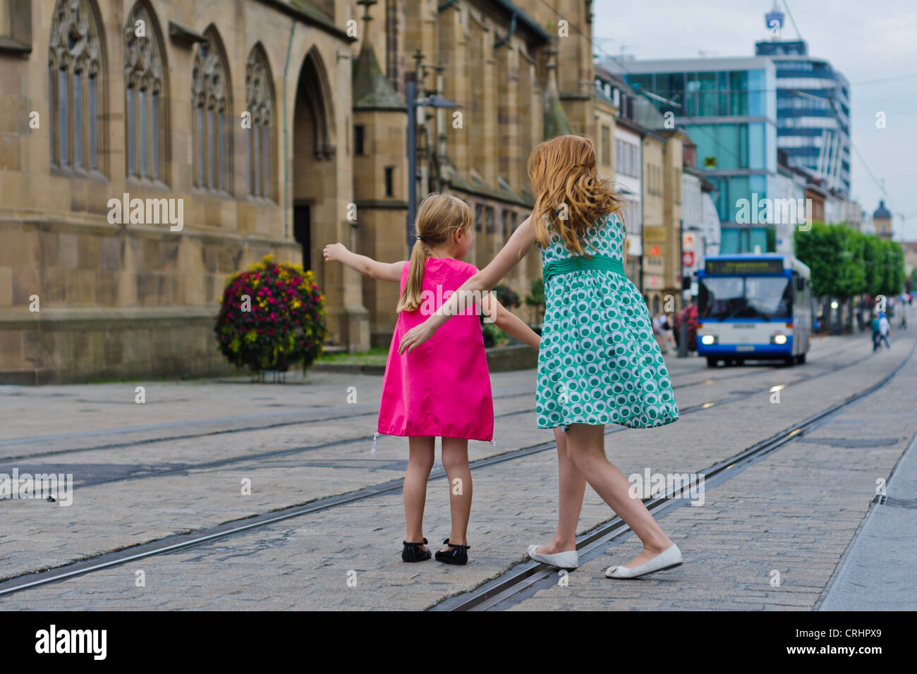 Two little young girls sisters in pink green cloth standing on rail track in front of St. Kilian´s Church Heilbronn - Stock Image