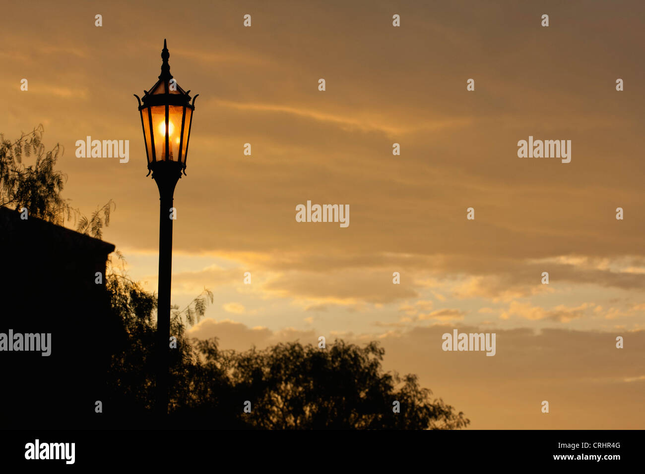 Street lamp illuminated at sunset - Stock Image