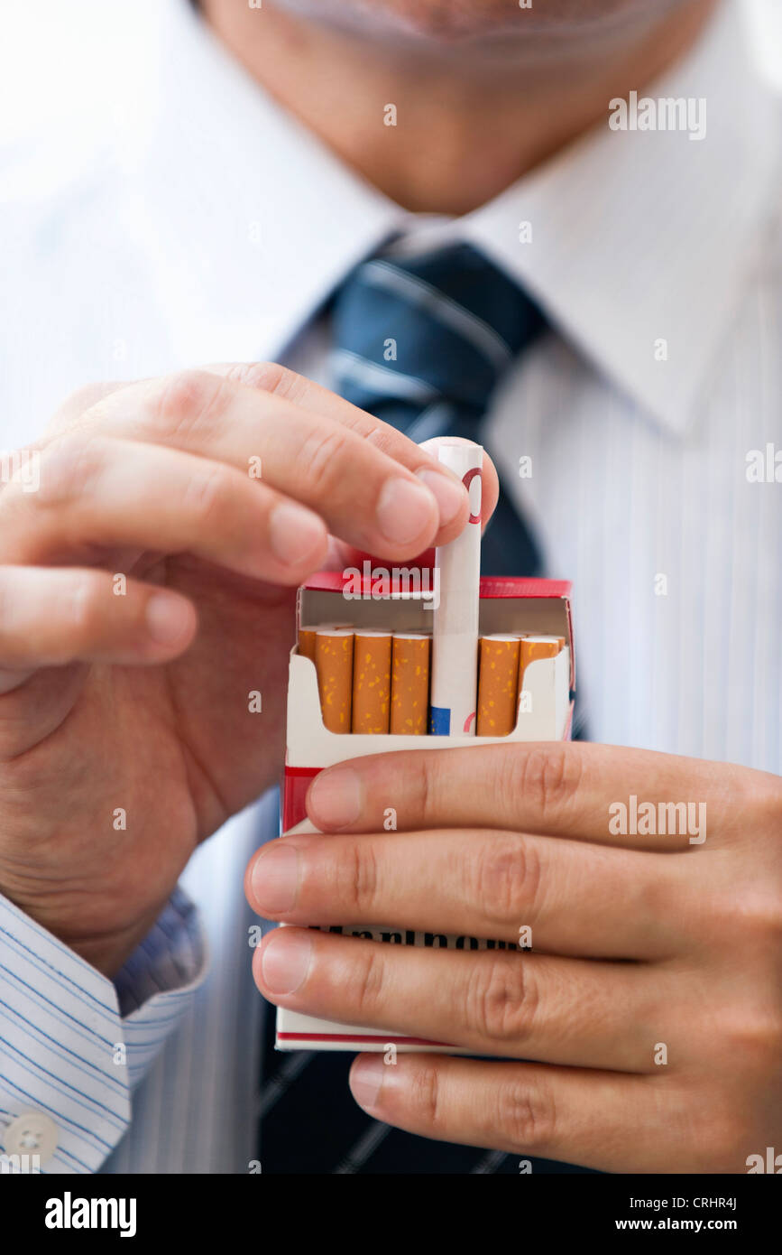 Removing rolled euro from cigarette pack - Stock Image