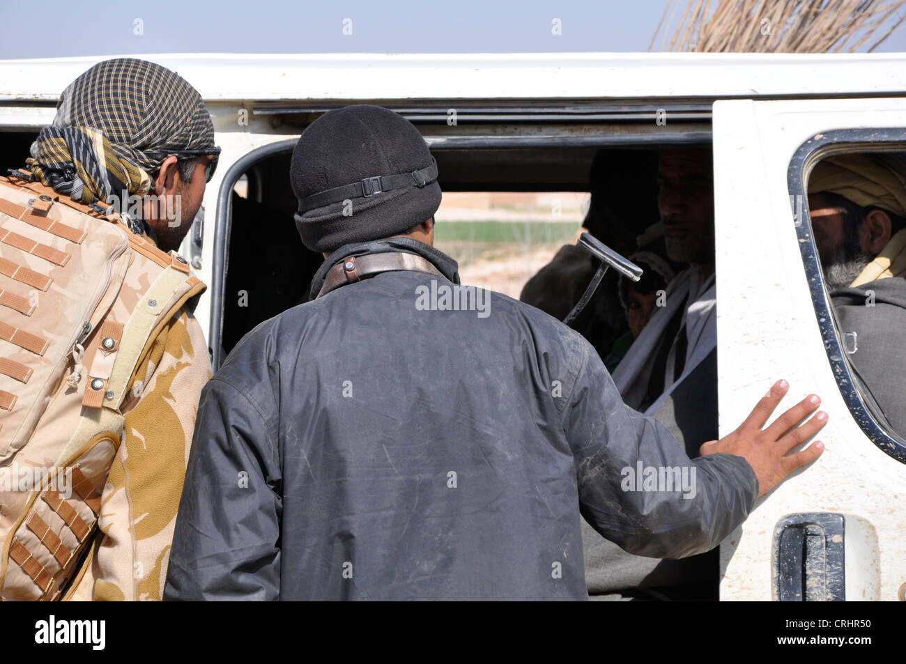 A british interpretor and Afghan policeman ask locals in afghanistan to vacate their vehicle. - Stock Image