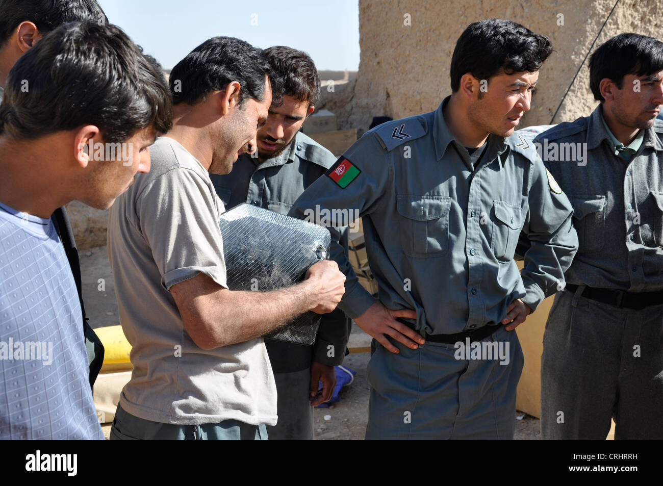 Afghan police officers stare in amazement after body armor issued by the British army takes a Taliban bullet. - Stock Image