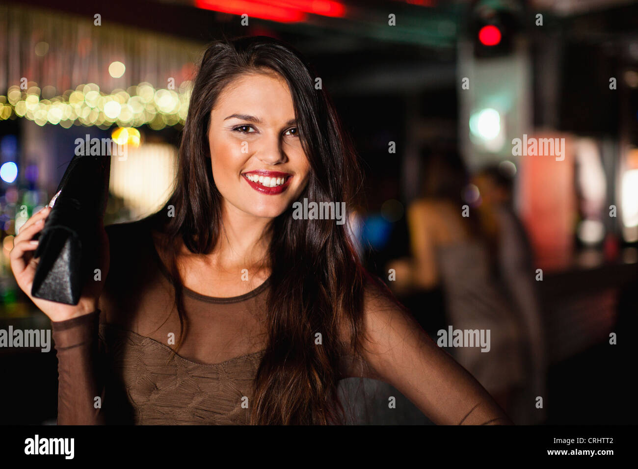 Smiling woman standing in bar - Stock Image
