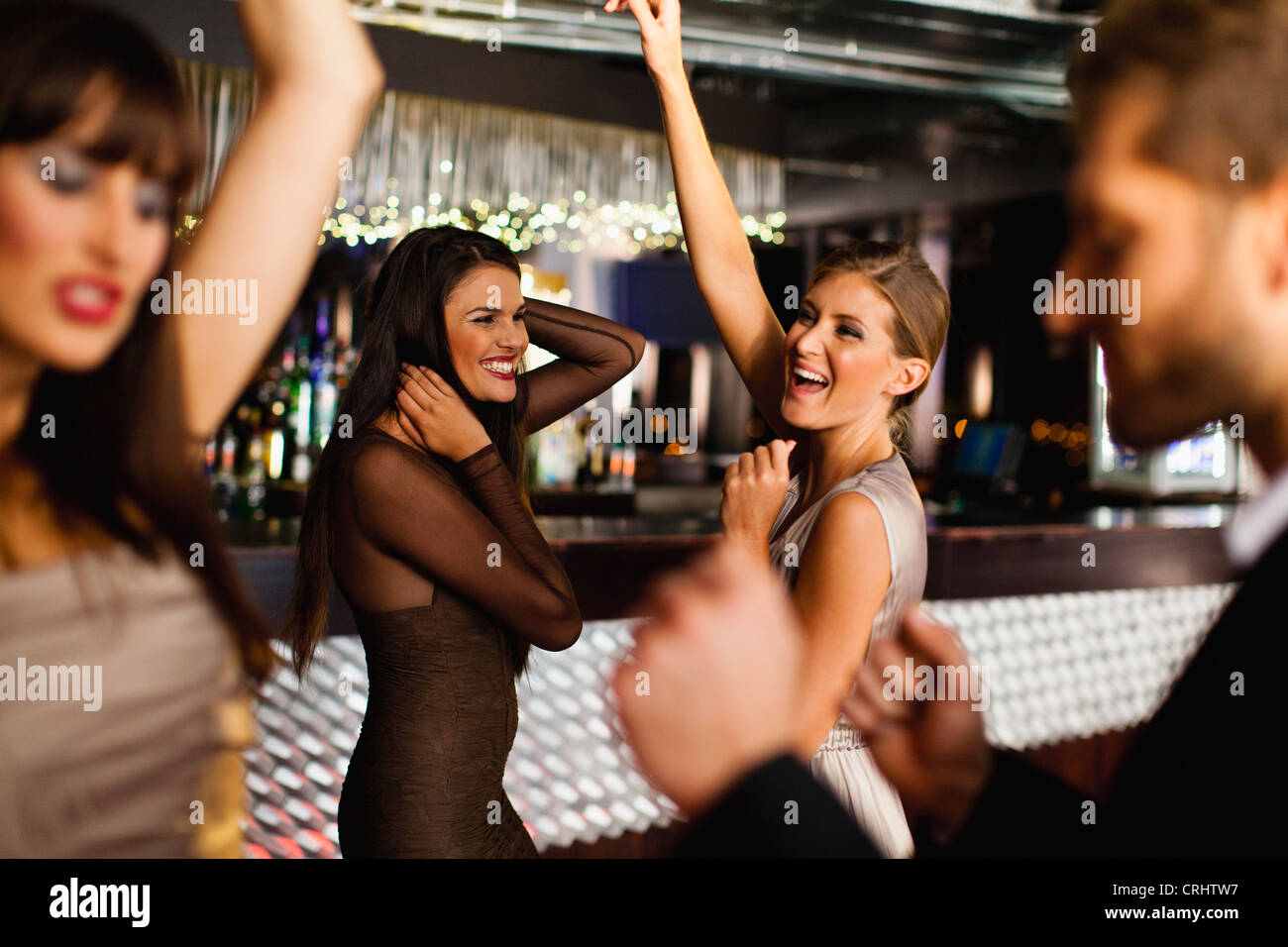 Smiling friends dancing in bar - Stock Image