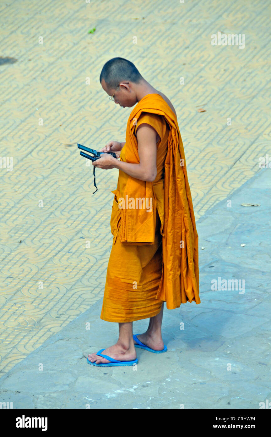 munk with two moblie phones in the strees of Phnom Penh, Cambodia Stock Photo