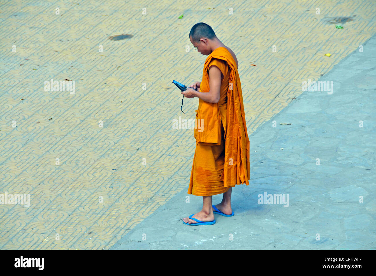 munk with moblie phone in the strees of Phnom Penh, Cambodia Stock Photo