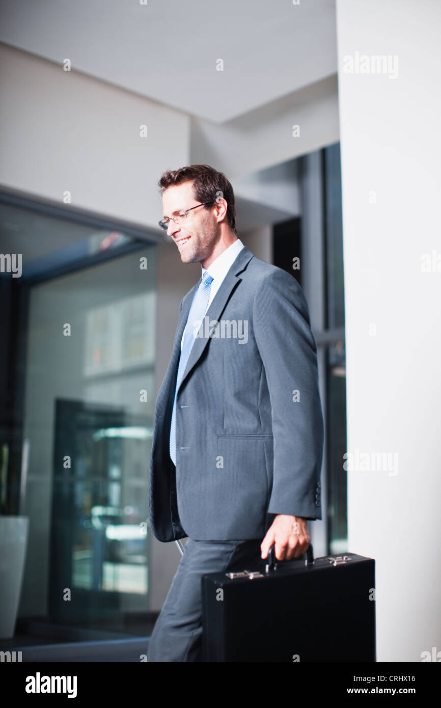 Businessman with briefcase in office - Stock Image
