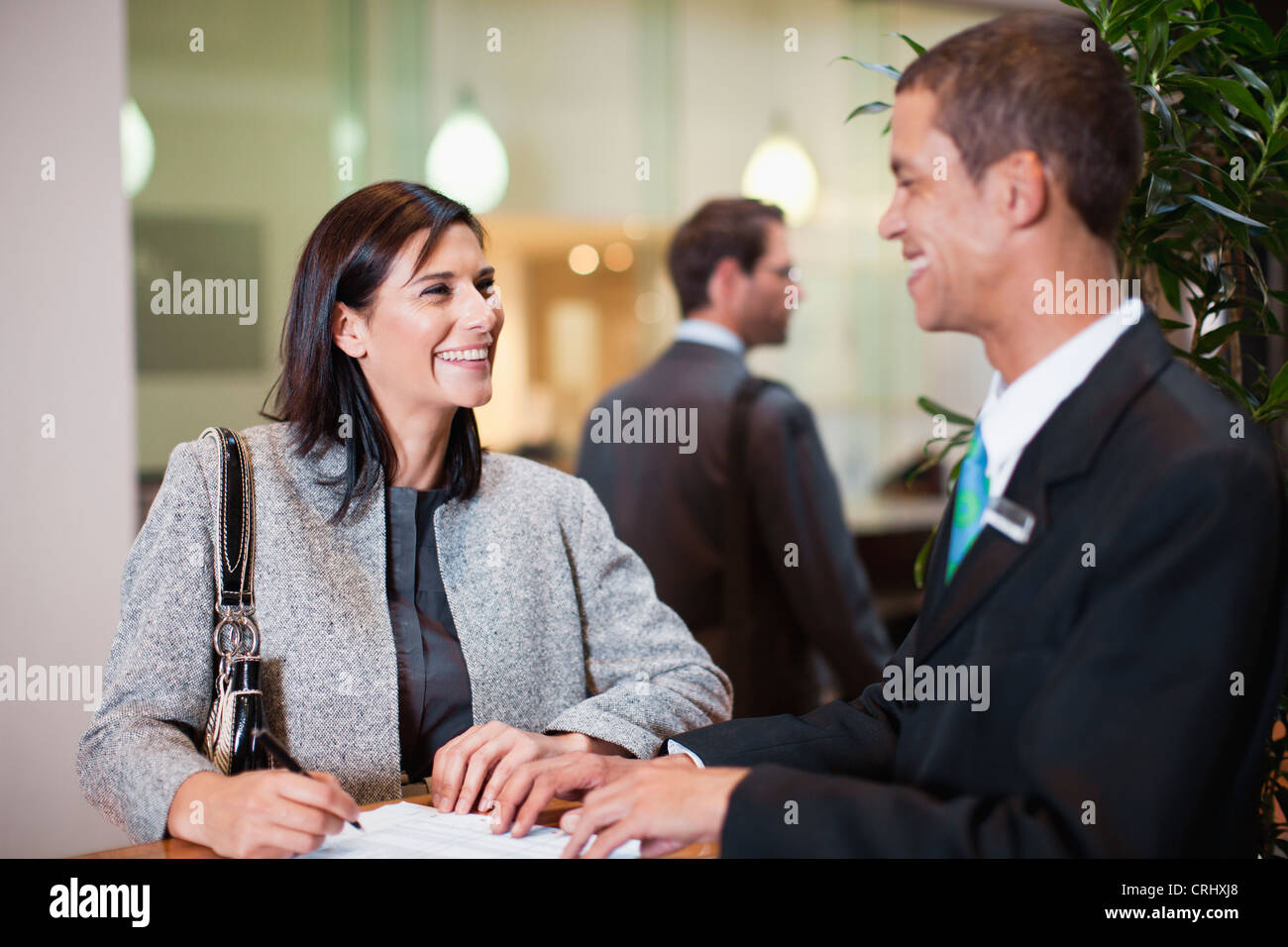 Businesswoman checking into hotel - Stock Image