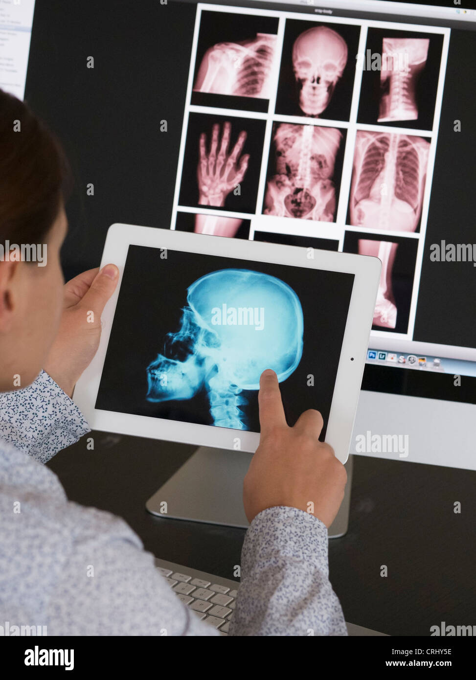 Doctor using iPad app to view xray images of patient - Stock Image