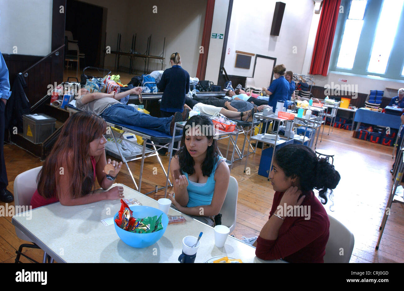 Young girls relax with refreshments after donating blood at a NHS National Blood Service collection centre. - Stock Image