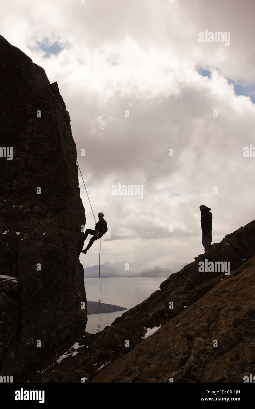 Climbers abseiling from the summit of the Inaccessible Pinnacle onto Sgurr Dearg in the Cuillin mountains - Stock Image