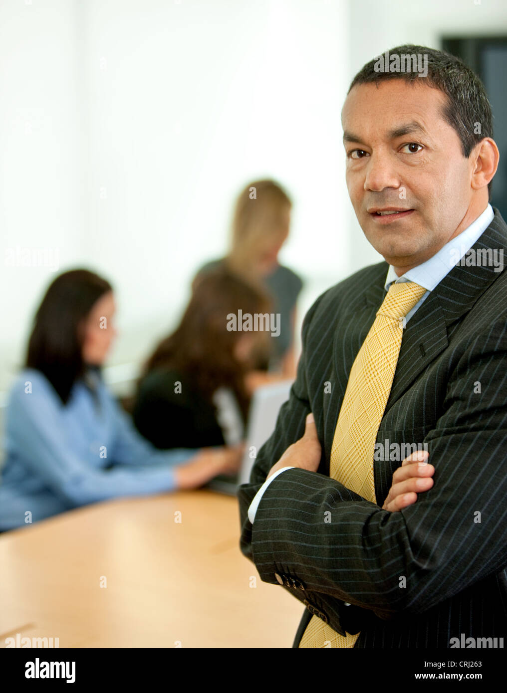 business man with arms crossed and people in the background working at a laptop - Stock Image