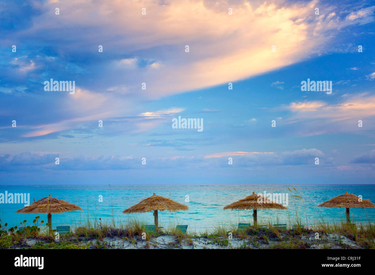 Reed umbellas and sunrise clouds. Turks and Caicos. Providenciales - Stock Image