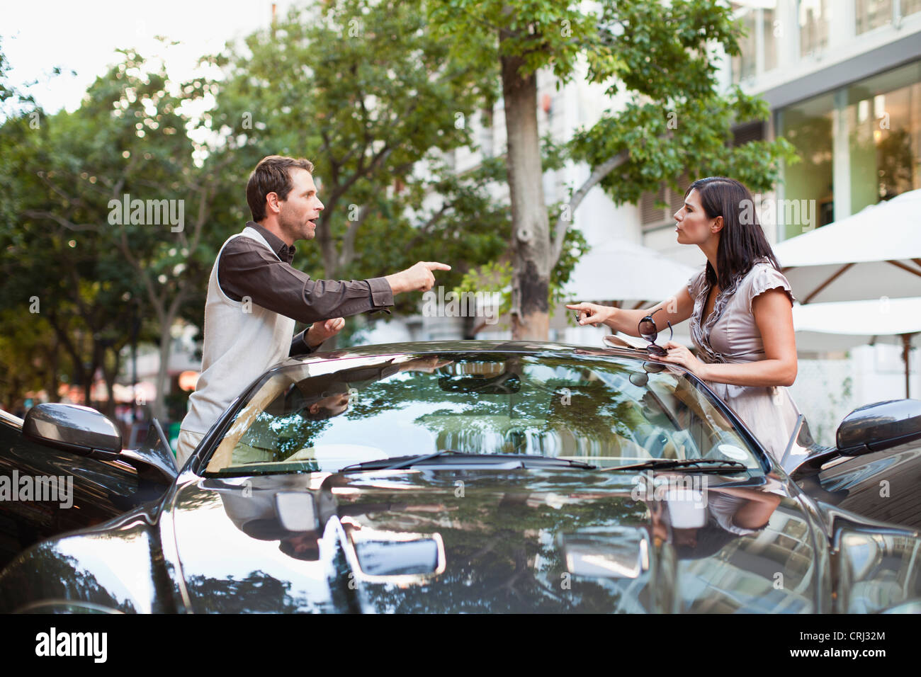 Couple arguing over sports car Stock Photo