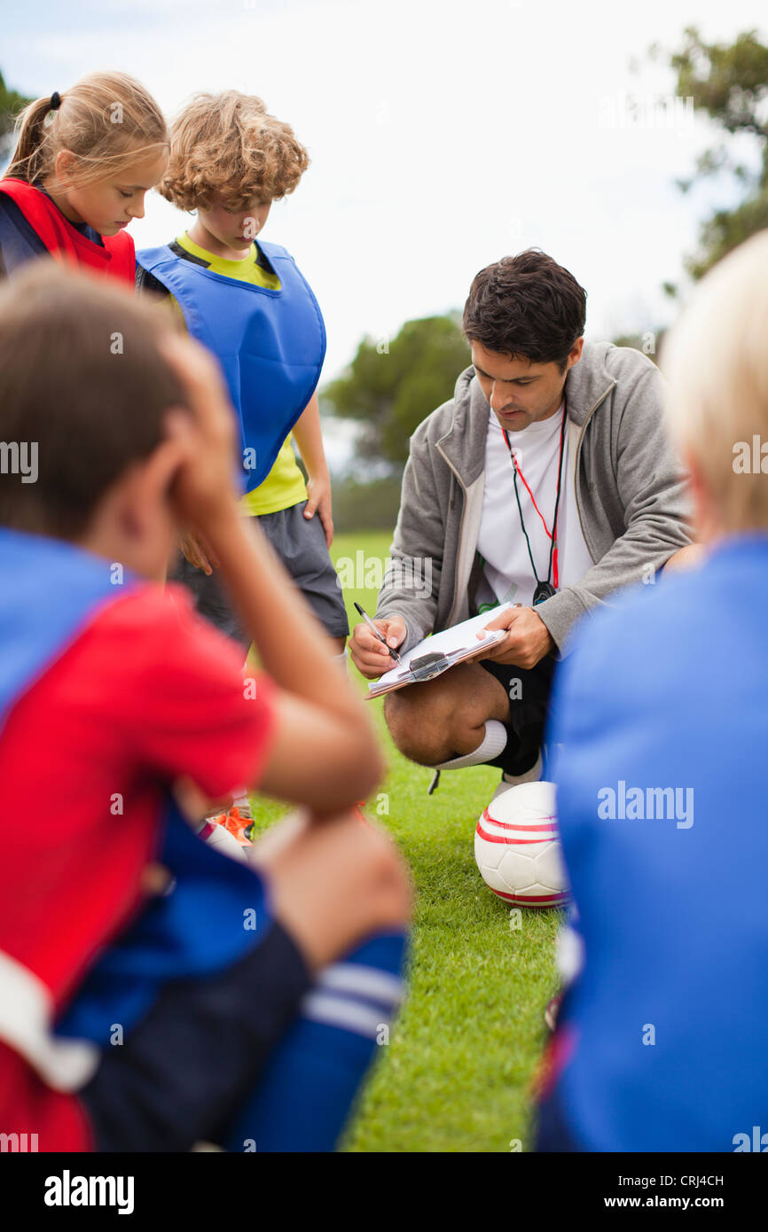 Coach talking to childrens soccer team Stock Photo
