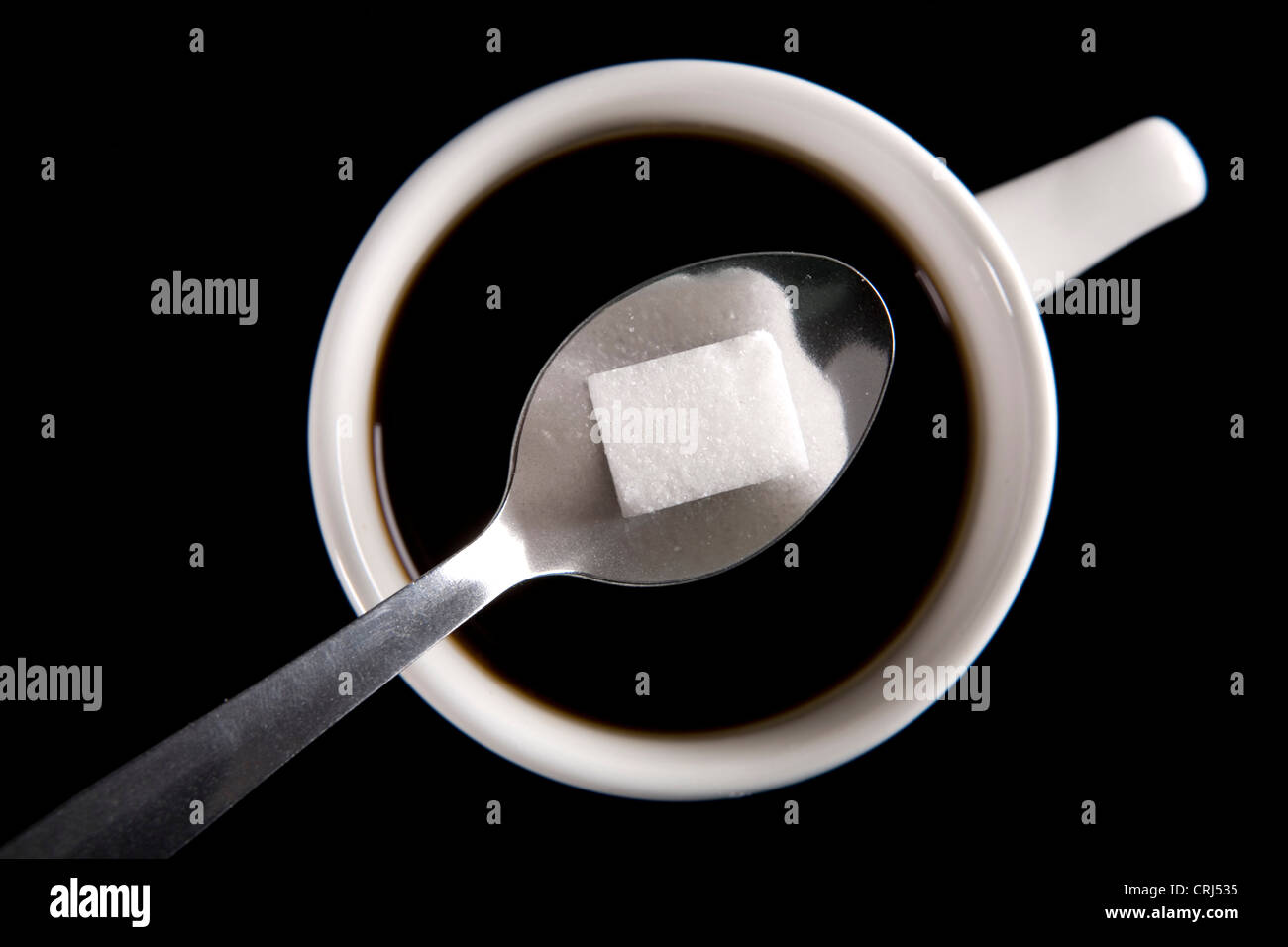 Sugar lump being added to a cup of coffee - Stock Image