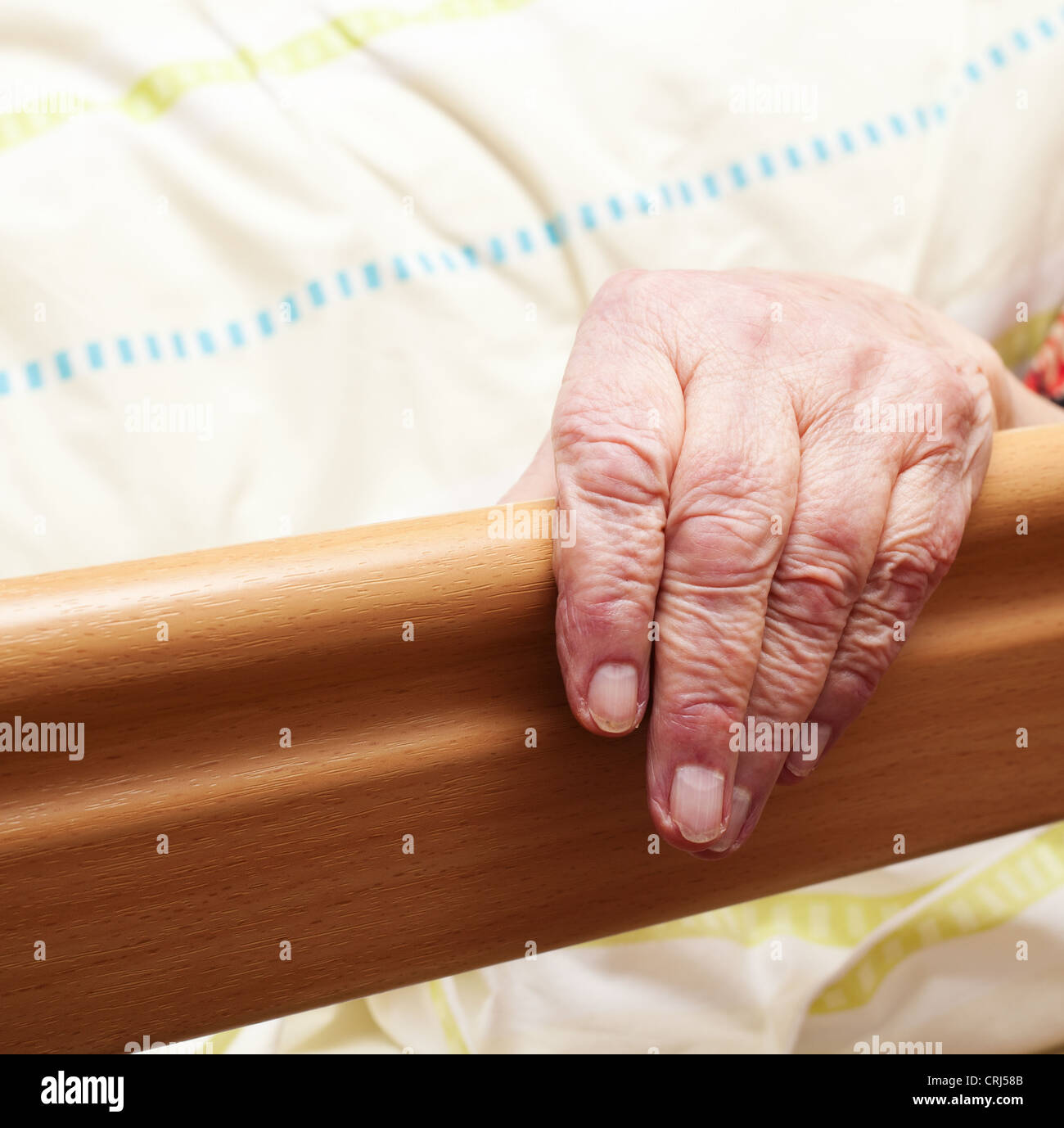 Care-dependent person lying in bed. - Stock Image
