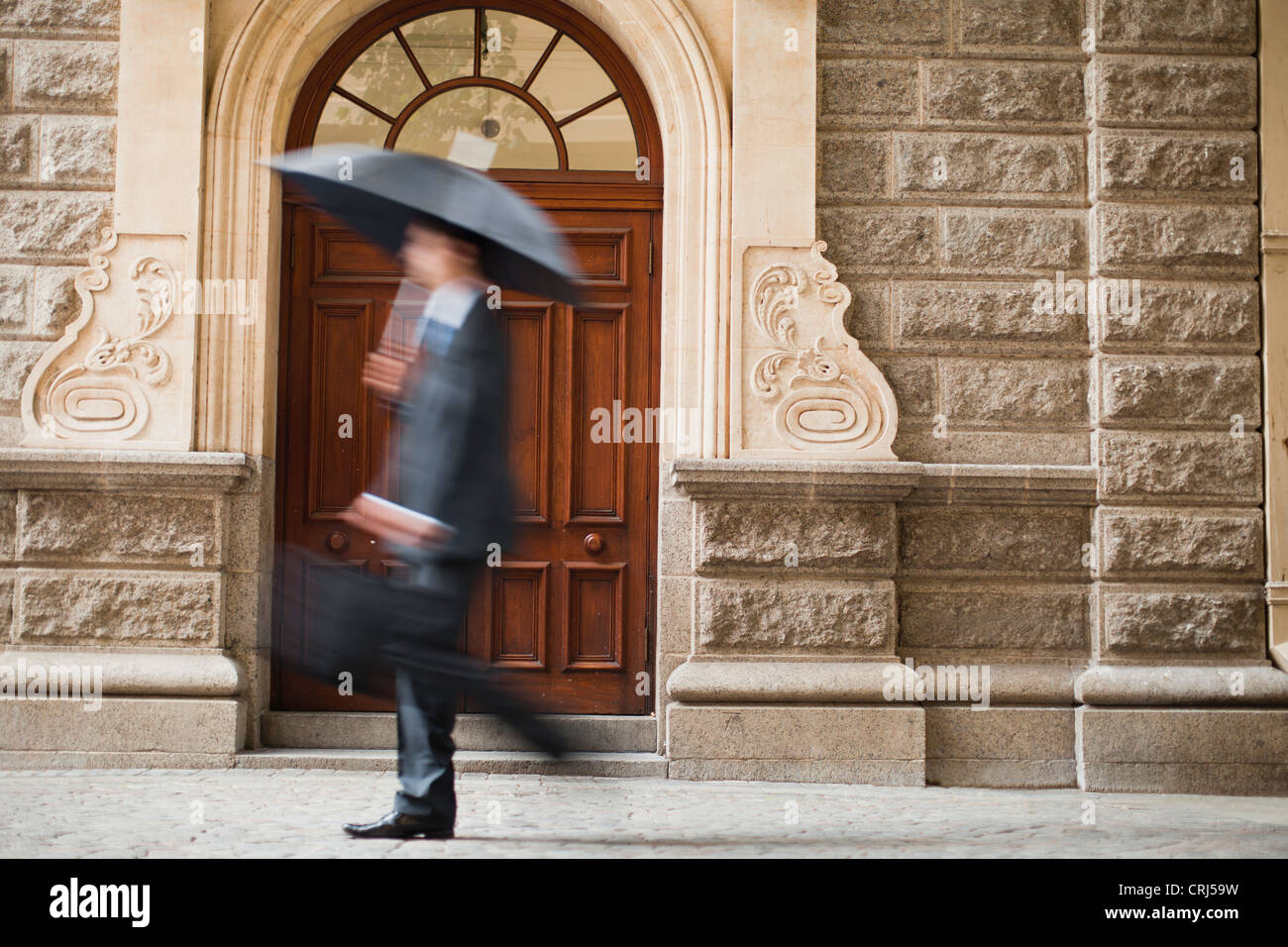 Businessman carrying umbrella on street - Stock Image