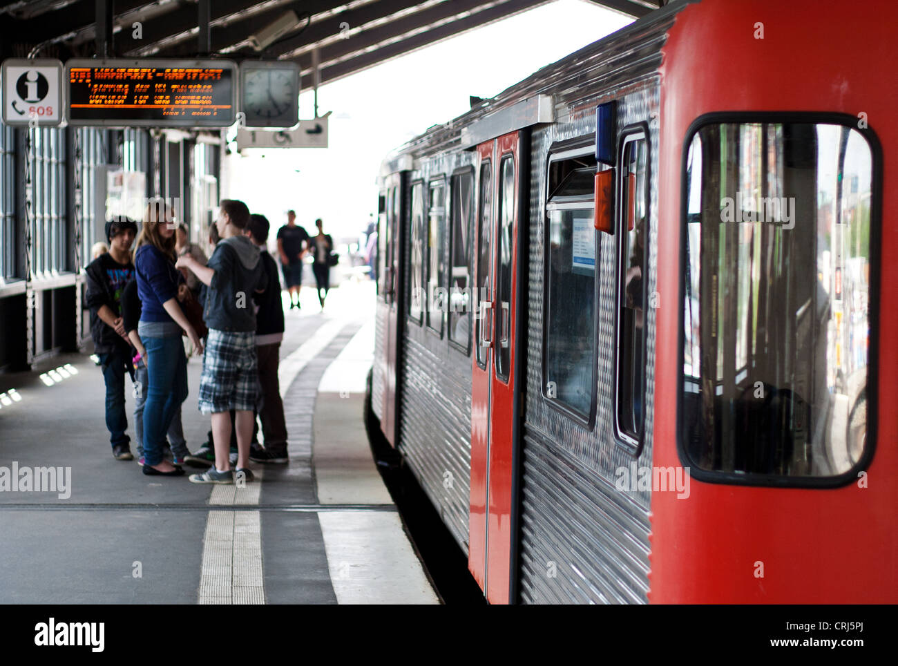 Group of young people waiting for tram at station Baumwall in Hamburg, Germany. Stock Photo