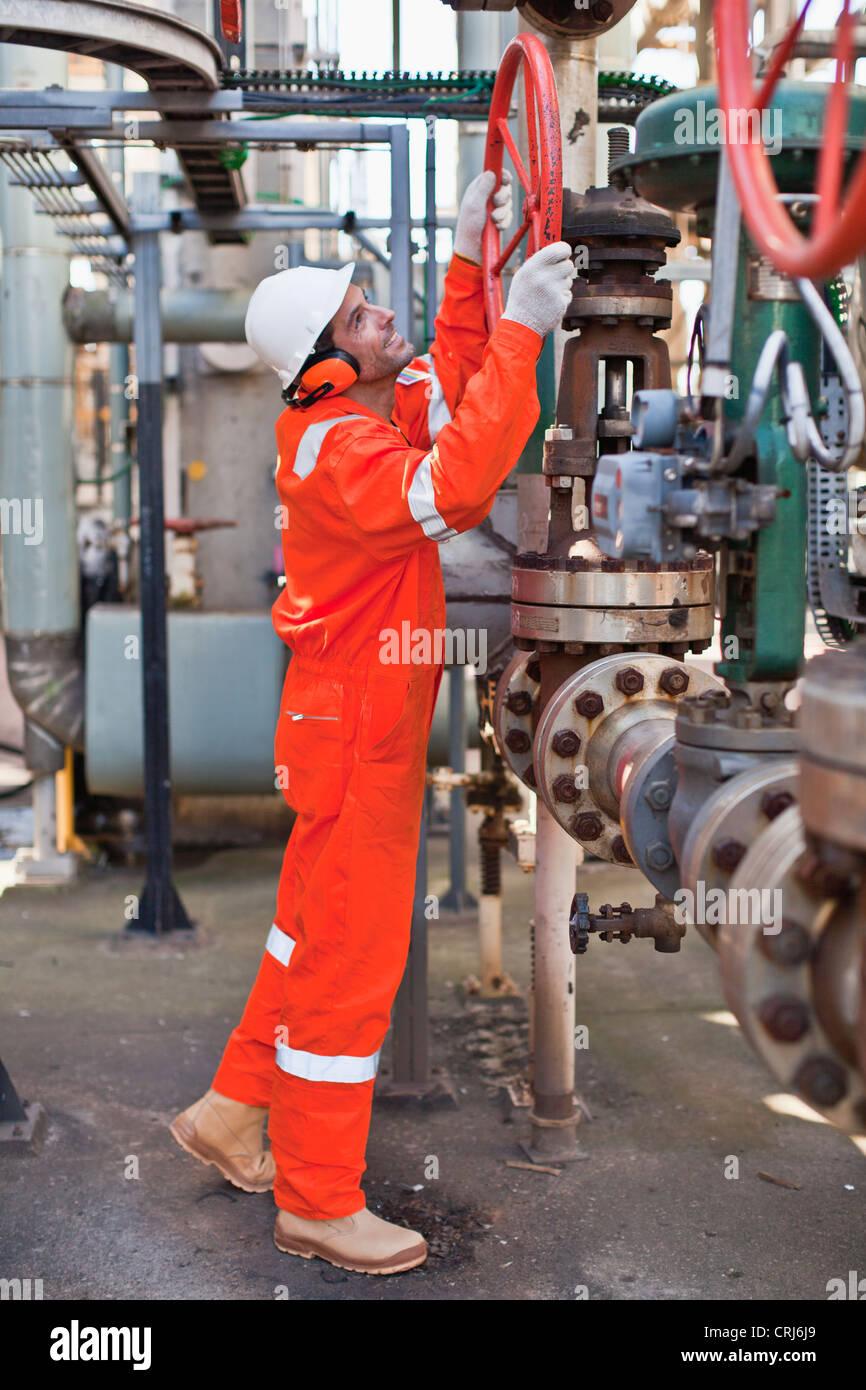 Worker adjusting gauge at oil refinery - Stock Image