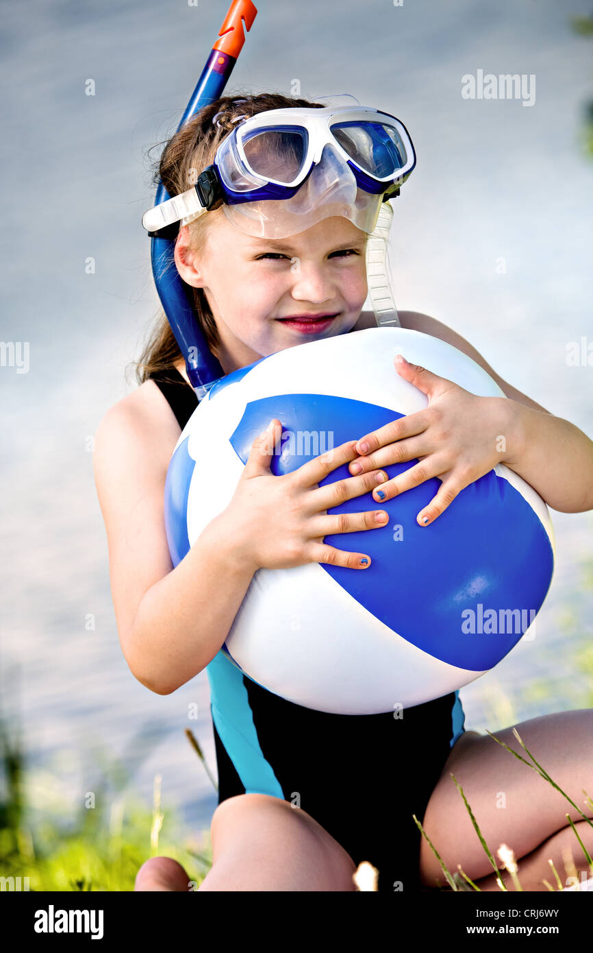 portrait of a little snorkeling girl with a ball - Stock Image