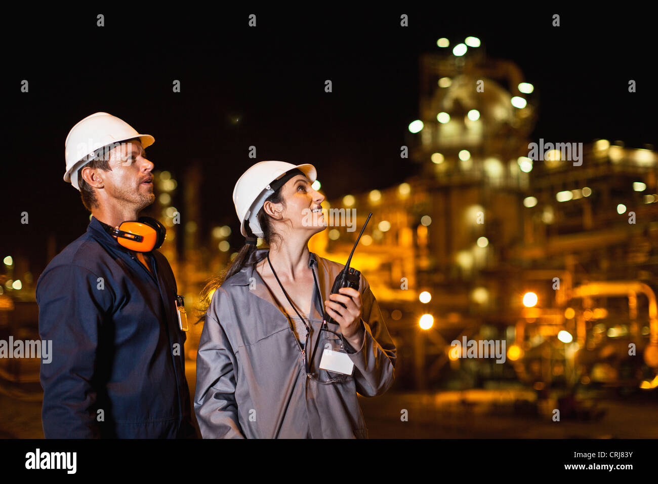 Workers talking at oil refinery - Stock Image