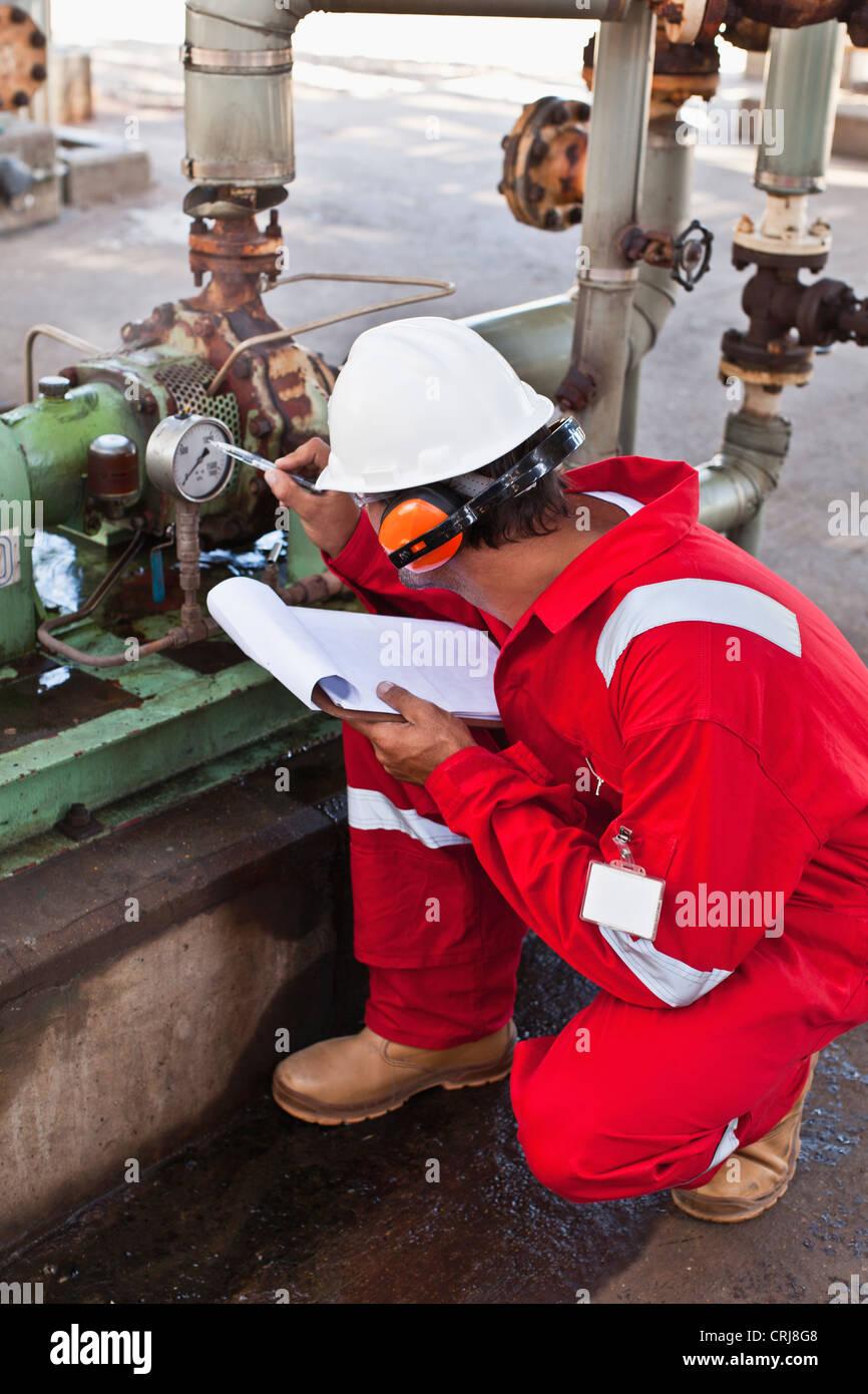 Worker noting gauge at oil refinery - Stock Image