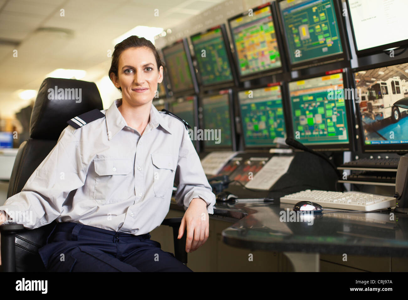 Woman working in security control room - Stock Image