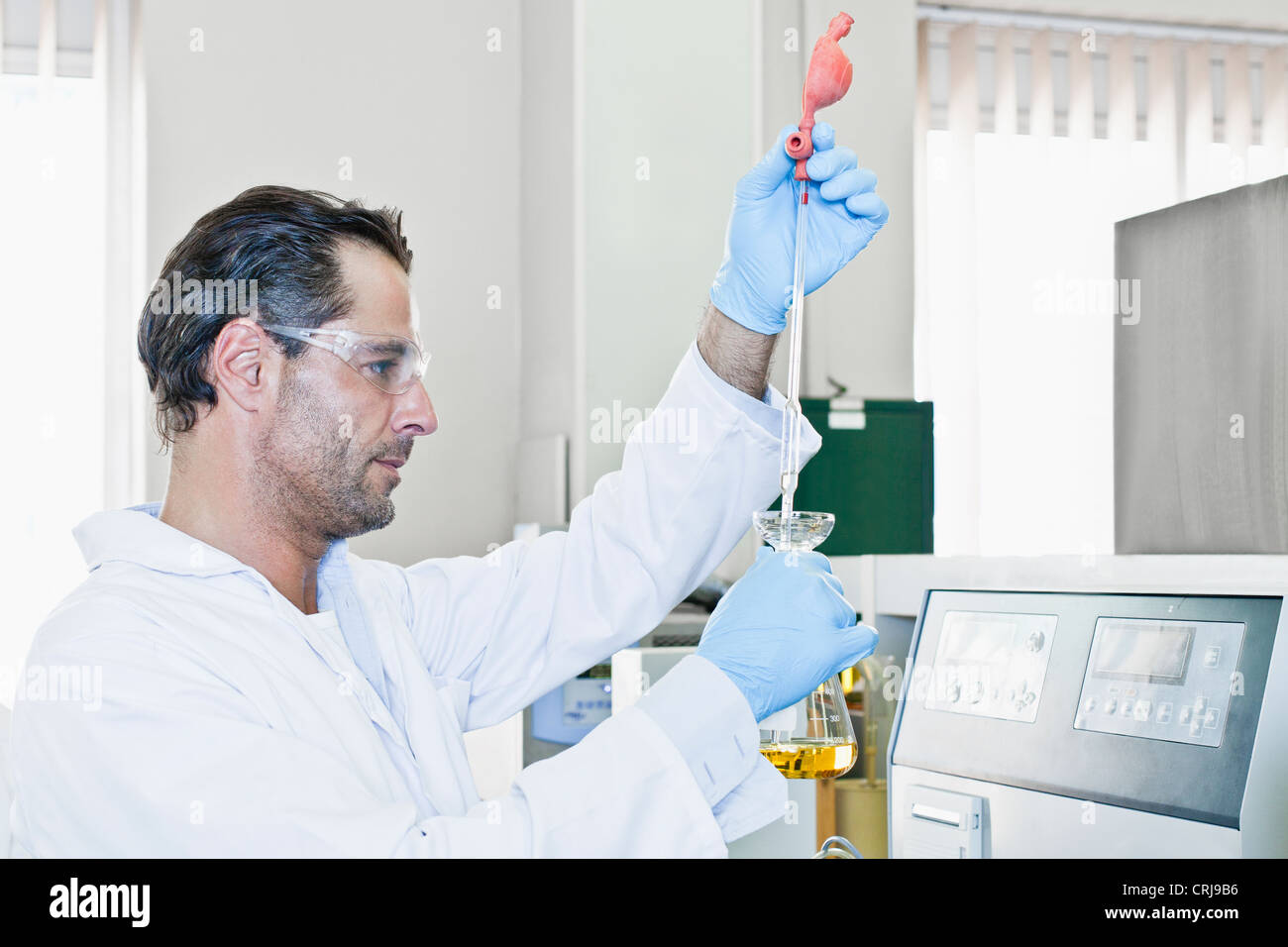 Scientist with pipette of liquid - Stock Image