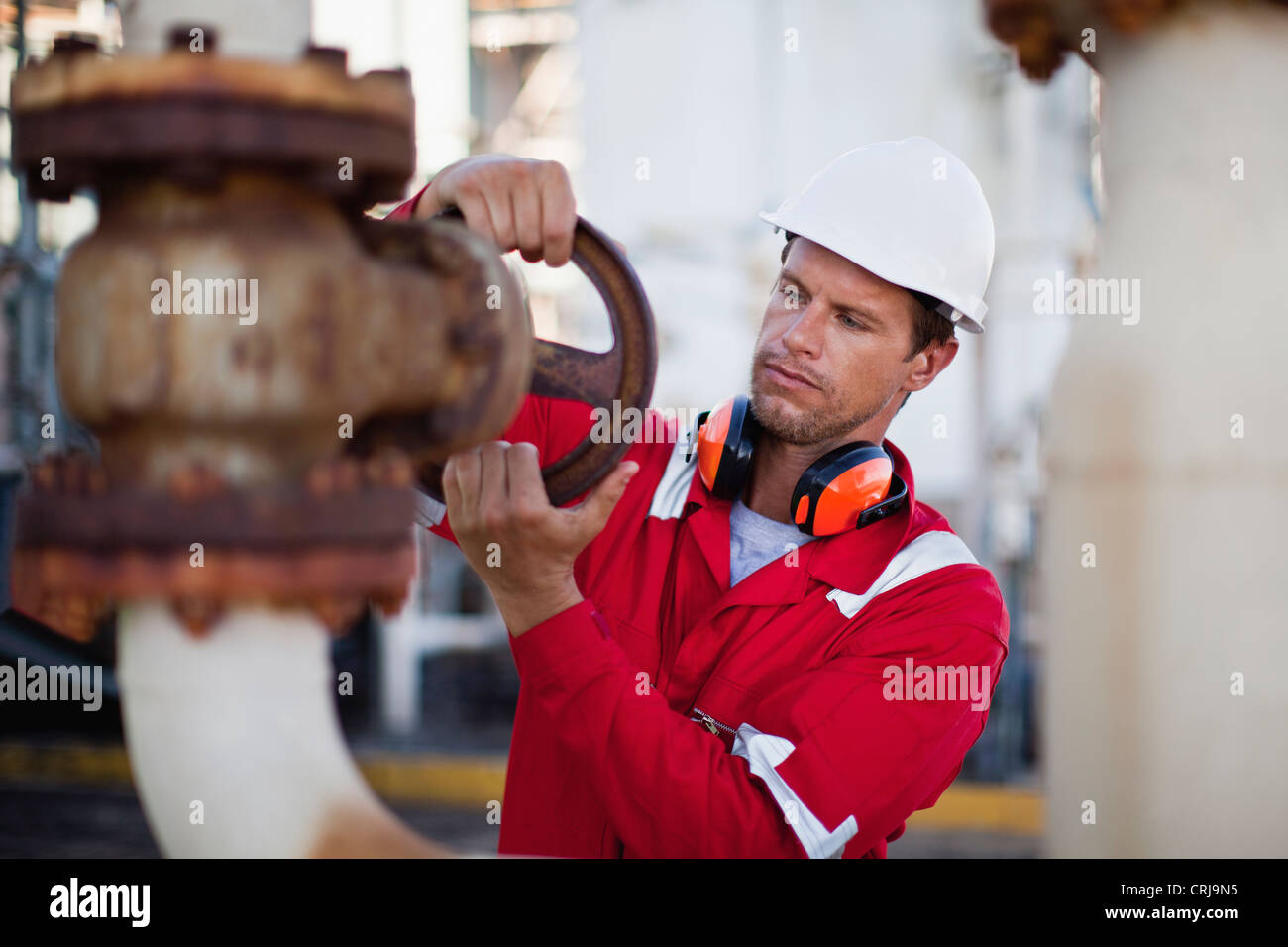 Worker adjusting gauge at chemical plant - Stock Image