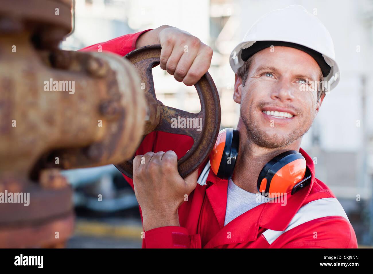 Worker adjusting gauge at chemical plant - Stock Image