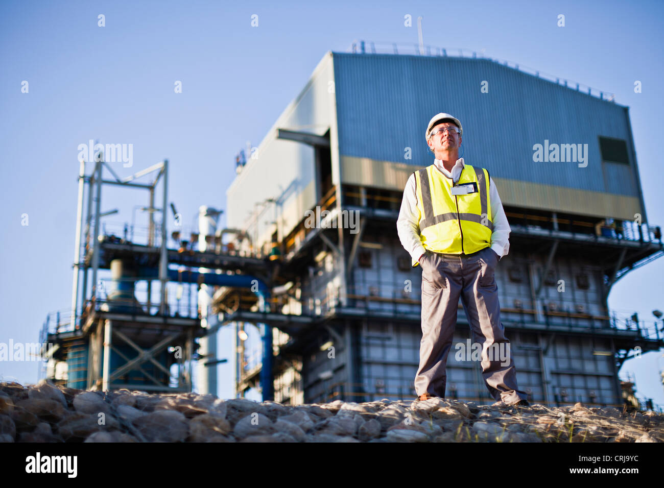 Worker standing at chemical plant - Stock Image