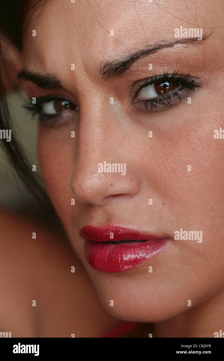 young woman with a lot of make-up frowning - Stock Image