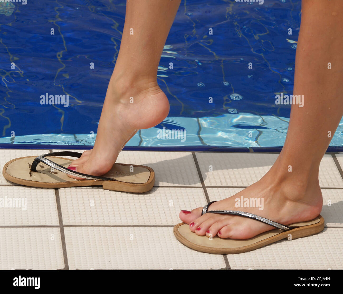 b572aae7d young woman s feet with varnished toenails in flip-flops at the edge of a  swimming