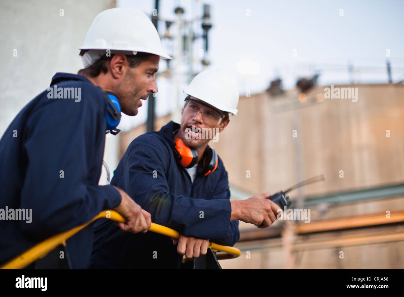 Workers talking at chemical plant - Stock Image