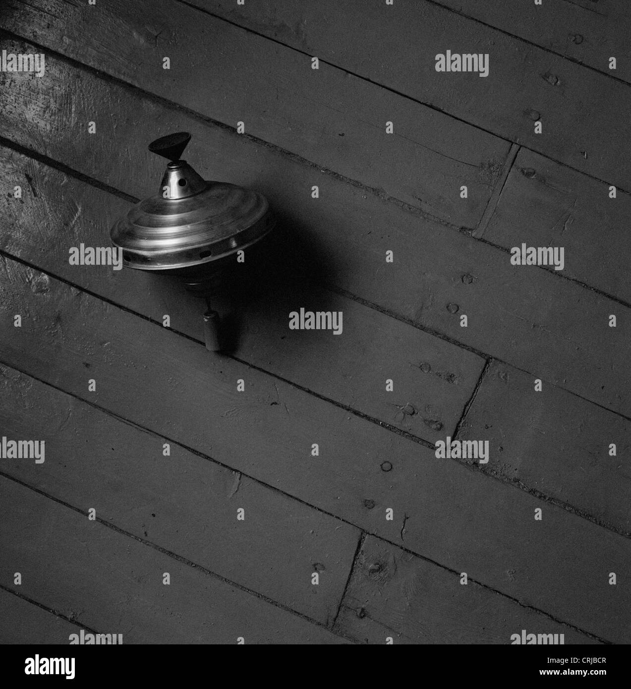 Humming top laying on a floor - Stock Image
