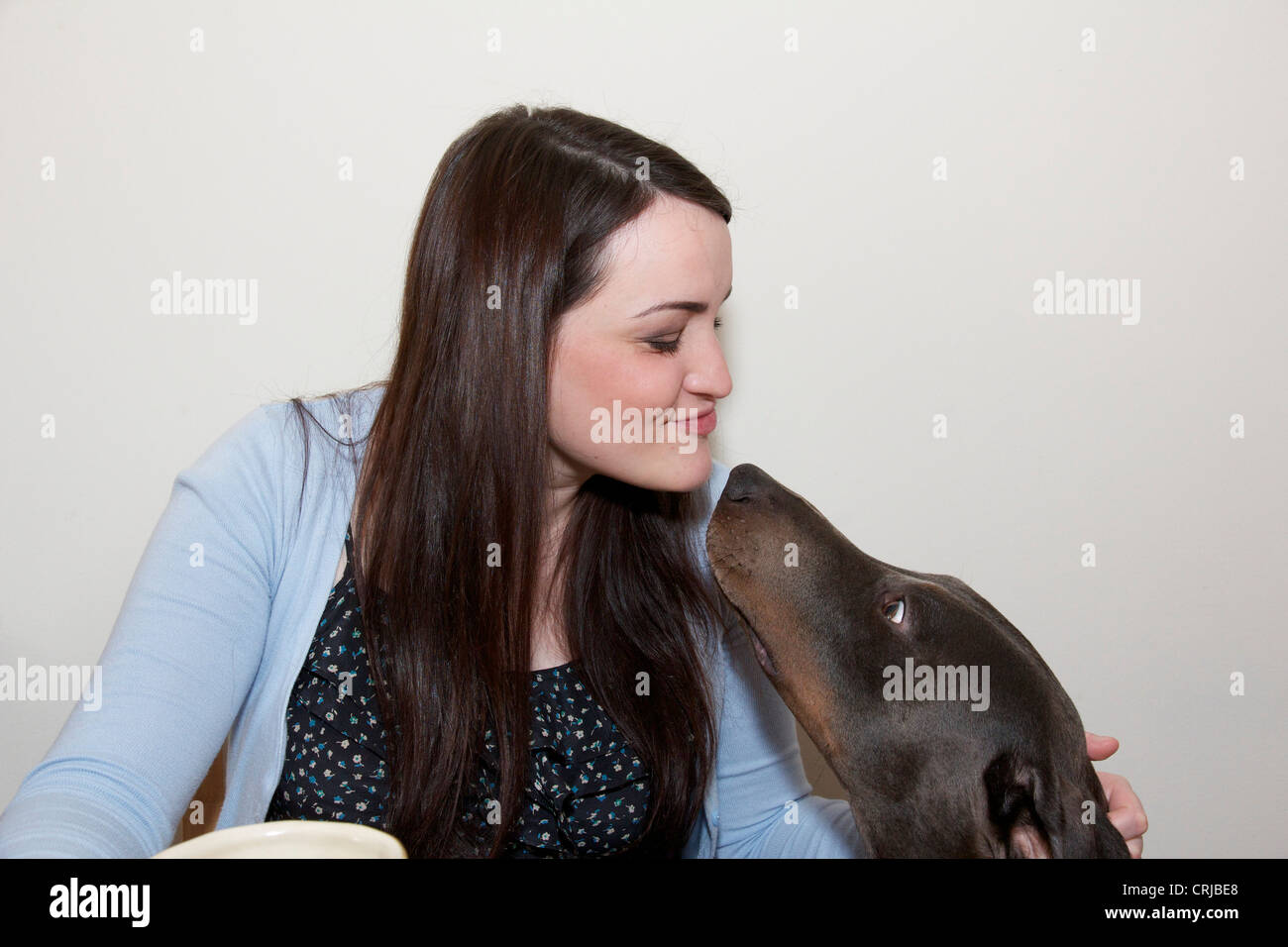 Young woman making kissy face with Doberman pinscher dog. - Stock Image