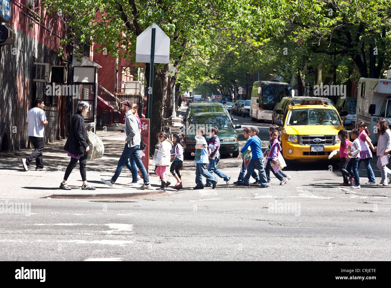 diverse group of multiethnic primary school children cross intersection with teachers & older monitors on west - Stock Image