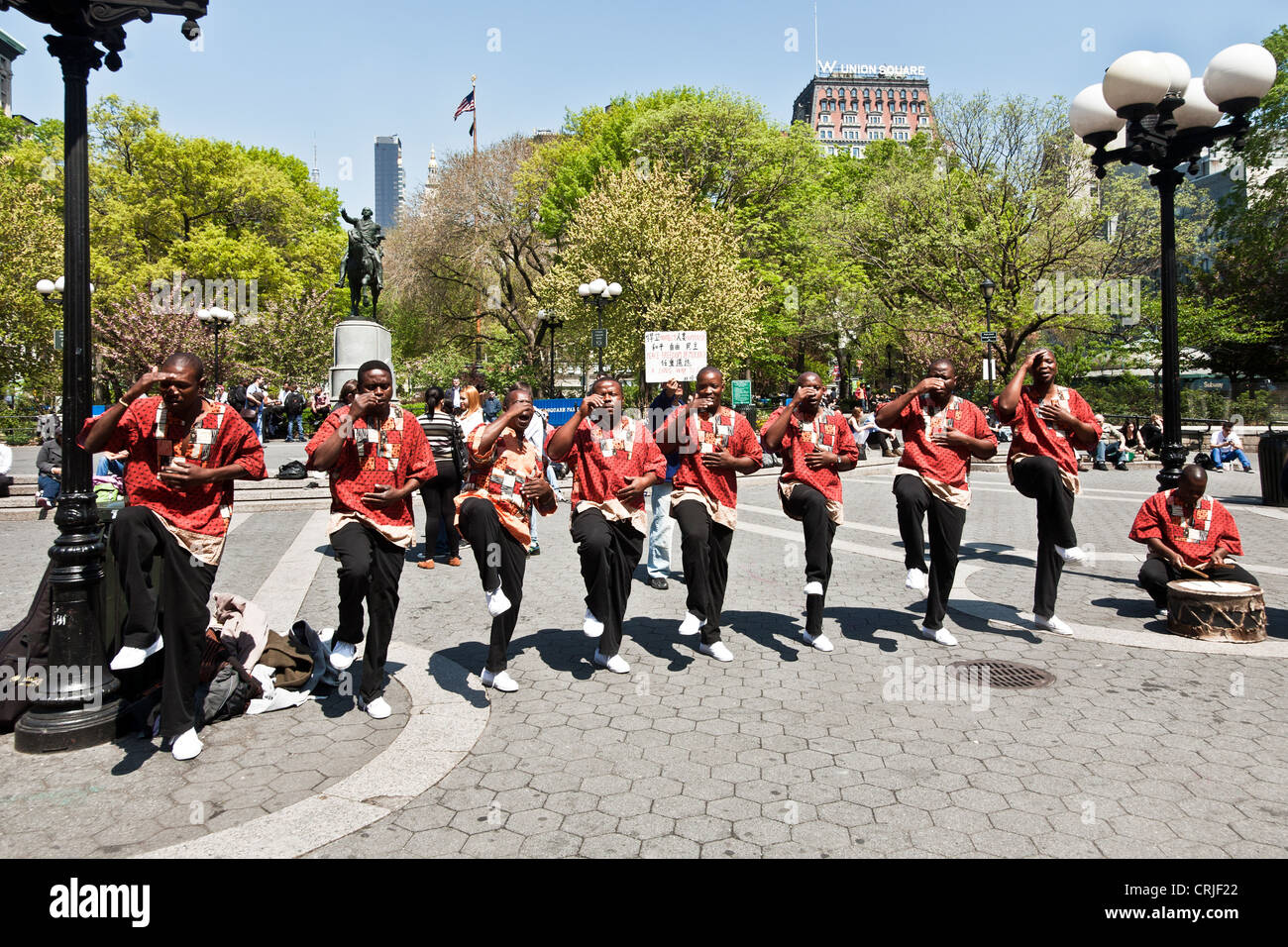 line of synchronized African dancers in colorful red shirts with drummer perform on a beautiful spring day in Union - Stock Image