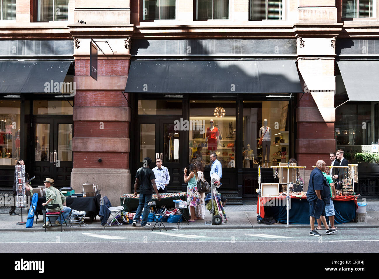 temporary sidewalk vendors provide a colorful shopping alternative to upscale boutiques behind them n Soho neighborhood - Stock Image
