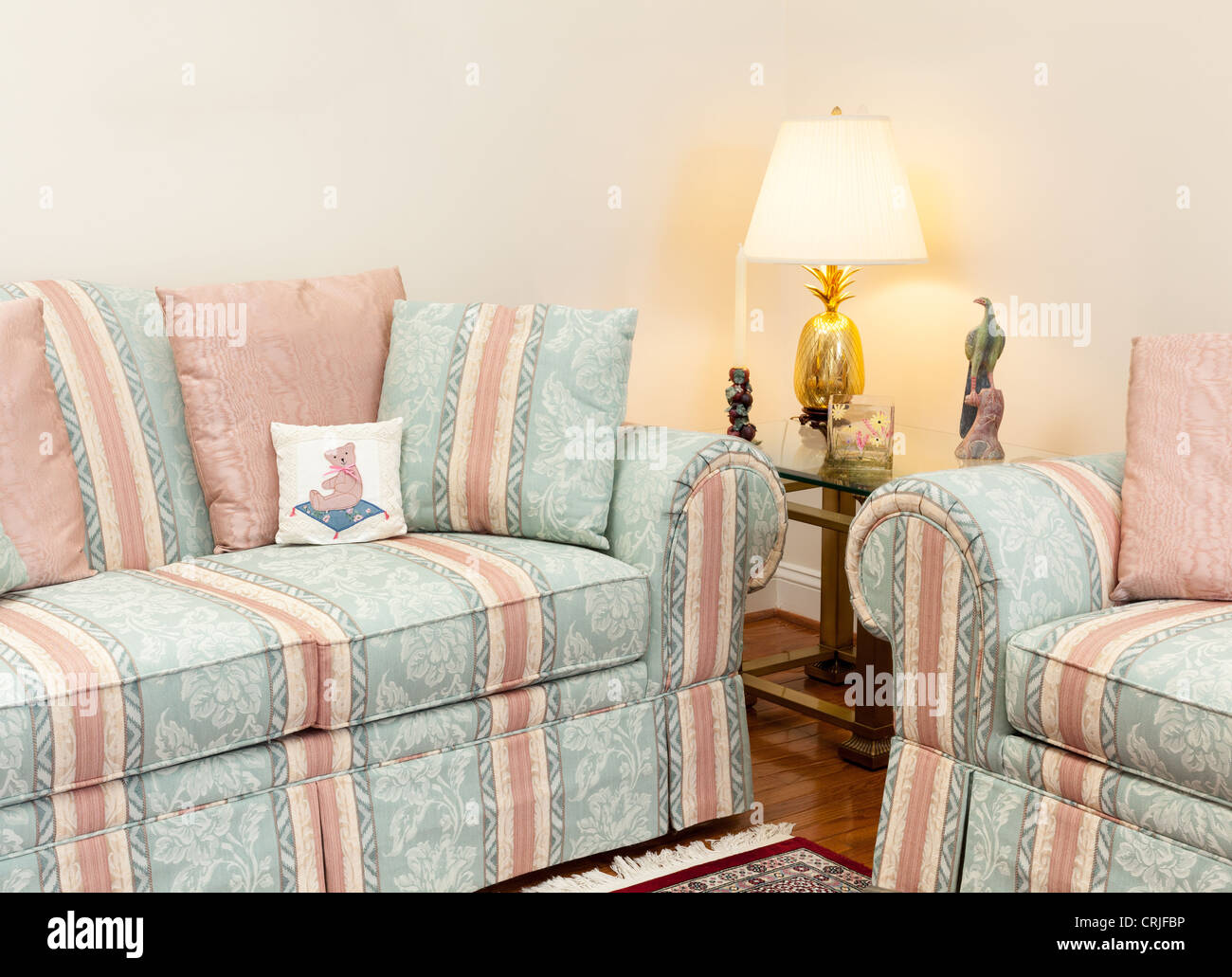 Modern living room with green and pink settees, glass table - Stock Image