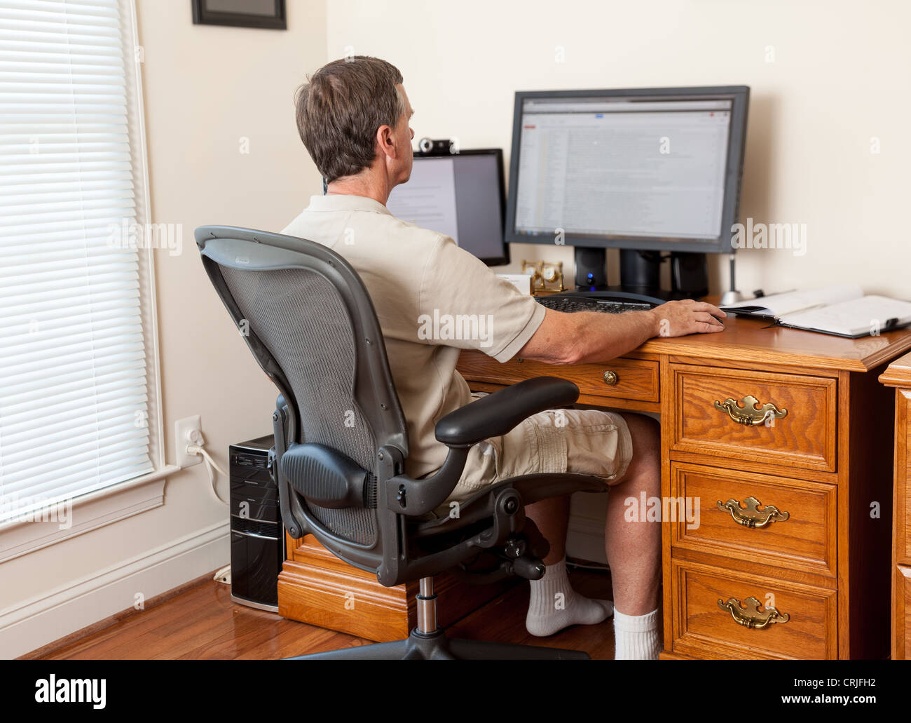 Man working from home office in shorts with desk with two monitors - Stock Image