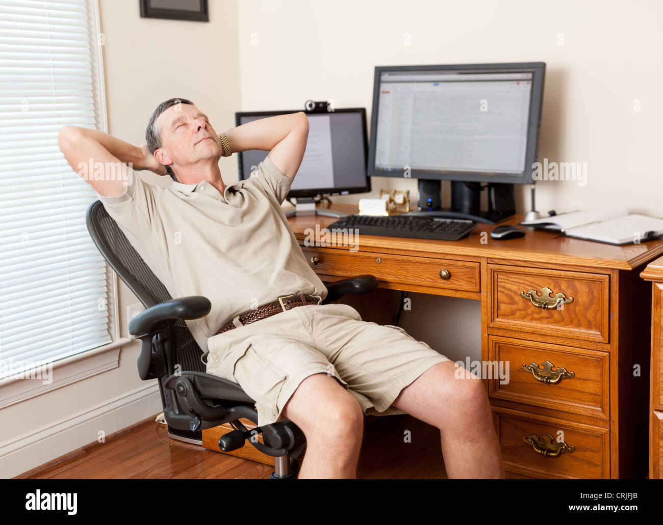 Man working from home office / thinking / slacking / sleeping / relaxing in shorts with desk with two monitors - Stock Image